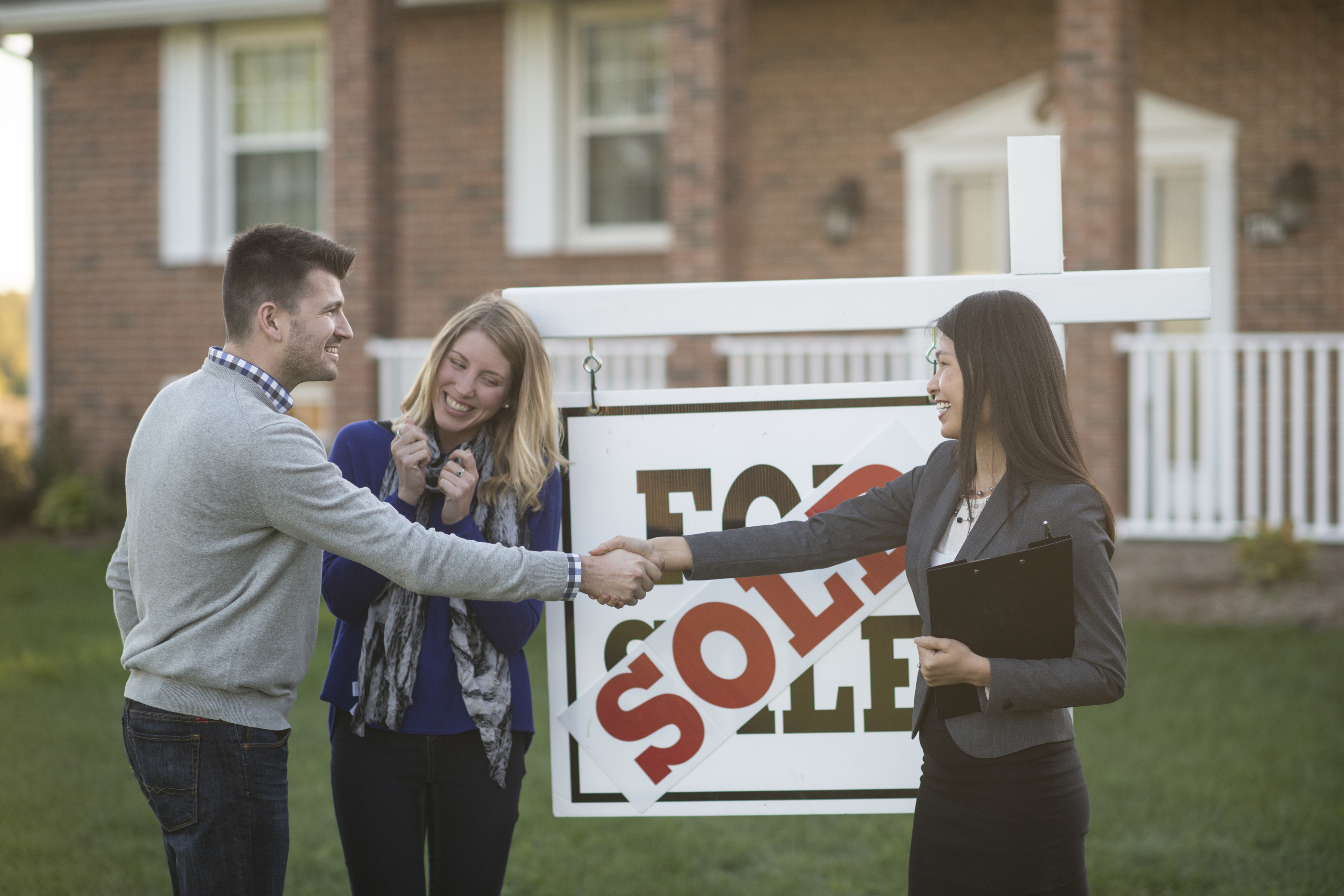 "A Caucasian husband and wife are standing outdoors in front of their new house. There is a ""sold"" sign on the lawn. The real estate agent is shaking hands with the husband, and the wife looks extremely happy."
